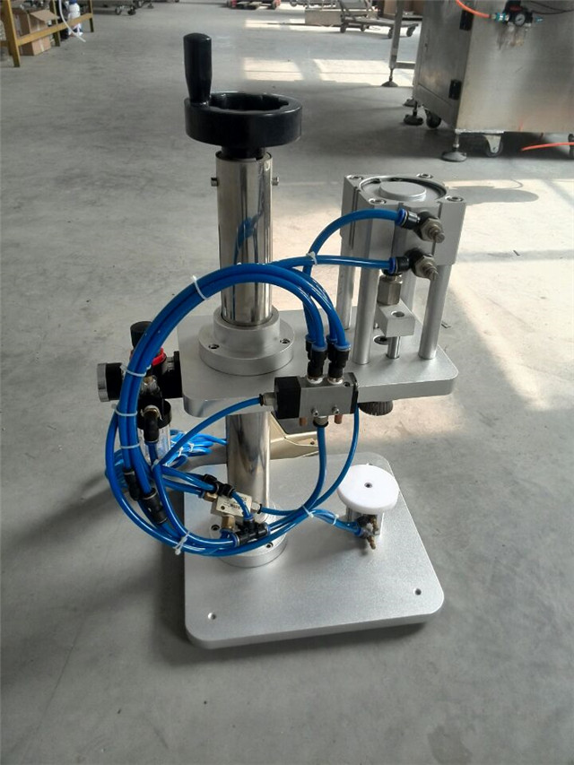 detailed view of glass bottles perfume crimping machine.jpg